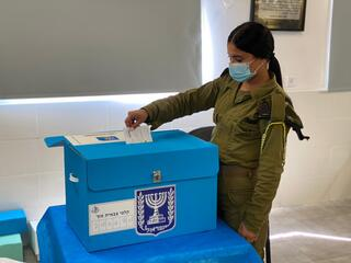 An IDF soldier casts her early ballot for the March 23 elections at a military polling station