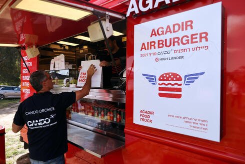 A man picks up a take away food delivery as he takes part in a demonstration whereby delivery drones from various companies flew in a joint airspace and were managed by an autonomous control system in Haifa, near Hadera