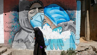 A Palestinian woman walks past a mural, amid the coronavirus disease (COVID-19) outbreak, in the central Gaza Strip