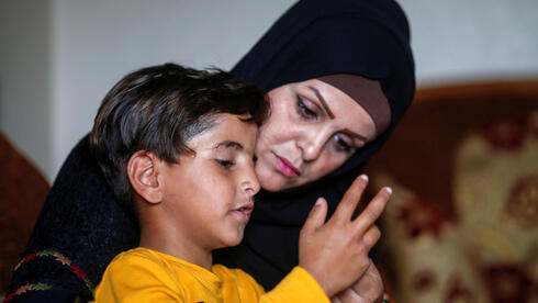Niveen Gharqoud sits with her son Amir at their home in the central Gaza Strip March 15, 2021