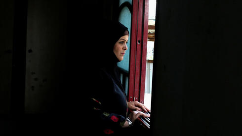 Niveen Gharqoud looks out from her home in the central Gaza Strip March 15, 2021. Picture taken March 15, 2021