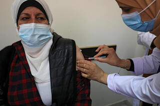 A Palestinian healthcare worker administers the COVID-19 vaccine to a patient