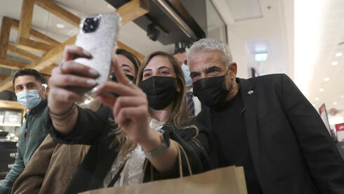 Yesh Atid leader Yair Lapid poses for a selfie with supporters as he campaigns at a mall in Haifa