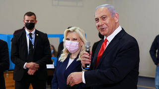 Prime Minister Benjamin Netanyahu voting with his wife Sara in Jerusalem on Tuesday