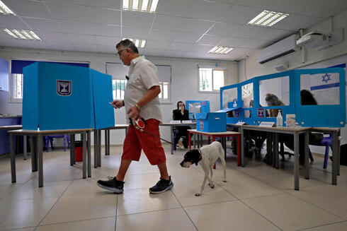 An Israeli man leads his dog as he casts his ballot at a polling station in Tel Aviv on March 23, 2021