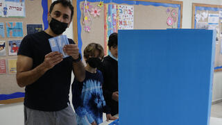 A voter holds up his ballot at a Tel Aviv polling station on Tuesday