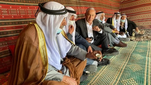 Prime Minister Benjamin Netanyahu shares coffee with Bedouin dignitaries in the village of Tirabin al-Sana in the Negev Desert during his campaign for re-election