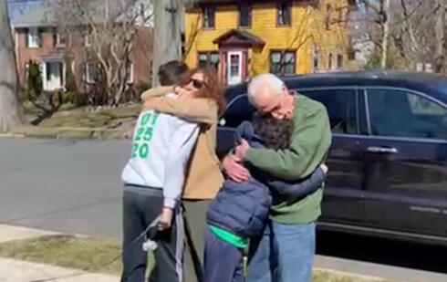 Esther and Bob Greenberg hug their grandsons Noah and Alex Barkin outside the children's home in Maplewood, New Jersey, March 2021