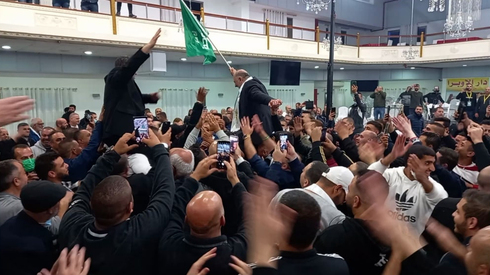Abbas (holding flag) and Ra'am supporters celebrate electoral gains in election for 24th Knesset