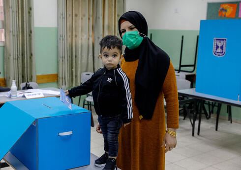 An Israeli Arab woman casts her vote in the March 23, 3021 elections in the town of Kfar Manda near Nazareth
