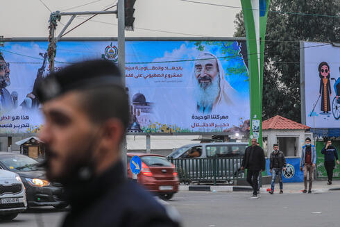 Palestinians walk next to a large poster of Hamas late leader Sheikh Ahmad Yassin during the 17th anniversay of his death in the streets of Gaza City