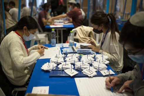 Workers count votes in Israel's national elections wearing and divided in groups by sheets of plastic masks to help curb the spread of the coronavirus, at the Knesset