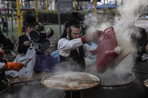 An ultra-Orthodox man dips prepares for Passover in Ashdod ahead of the holiday that begins Saturday