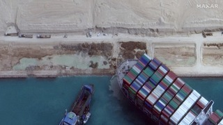 A tug boat near the stranded Ever Given container ship in the Suez Canal on  Sunday