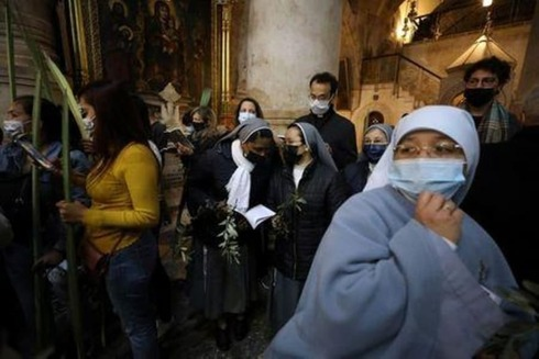 Christian worshippers and nuns hold palm fronds during a Palm Sunday procession in the Church of the Holy Sepulchre in Jerusalem