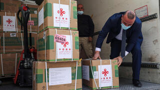 Staff members of the Palestinian Ministry of Health unload a shipment of the Sinopharm COVID-19 vaccines donated by the Chinese government in the city of Ramallah in the West Bank