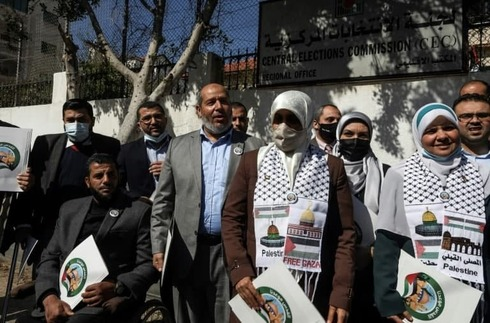 Senior Hamas official Khalil al-Haya poses with supporters outside the electoral commission headquarters in Gaza City