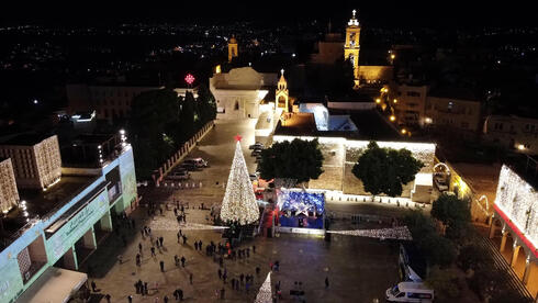 An aerial view shows people taking part in a Christmas tree-lighting ceremony in Manger Square outside the Church of the Nativity, during the coronavirus disease (COVID-19) outbreak, in Bethlehem, in the Israeli-occupied West Bank