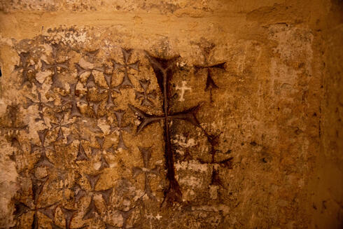 Crosses etched into the ancient stone wall of the Saint Helena chapel are seen inside the Church of the Holy Sepulchre in Jerusalem