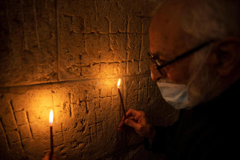 Father Samuel Aghoyan, the Armenian superior at the Church of the Holy Sepulchre holds candles to illuminate crosses etched into the ancient stone wall of the Saint Helena chapel inside the church