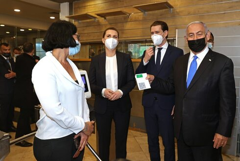 """Prime Minister Benjamin Netanyahu, right, holds a """"Green Pass,"""" for citizens vaccinated against COVID-19, as he visits a fitness gym with Austrian Chancellor Sebastian Kurz, second right, and Danish Prime Minister Mette Frederiksen, left, to observe how the pass is used, in Modi'in"""