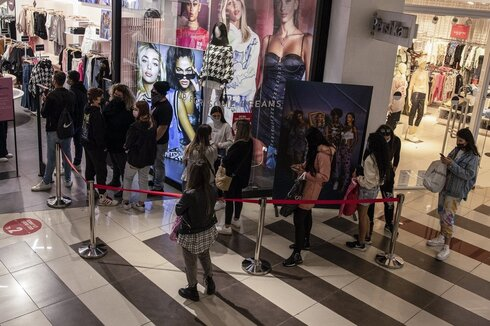 consumers line up to enter a clothing store at a shopping center in the city of Beersheba