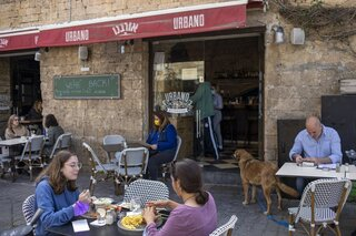 People eat in a restaurant in Tel Aviv as restrictions are eased following months of government-imposed shutdowns