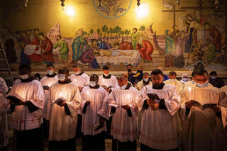Priests wearing face masks pray during Easter Sunday Mass led by the Latin Patriarch at the Church of the Holy Sepulchre in the Old City of Jerusalem, April 4, 2021
