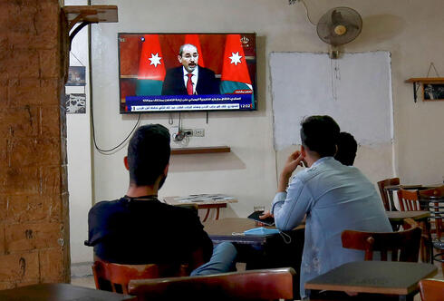 Men watching Jordan's Deputy Prime Minister Ayman Safadi address the nation after an alleged coup attempt in capital of Amman