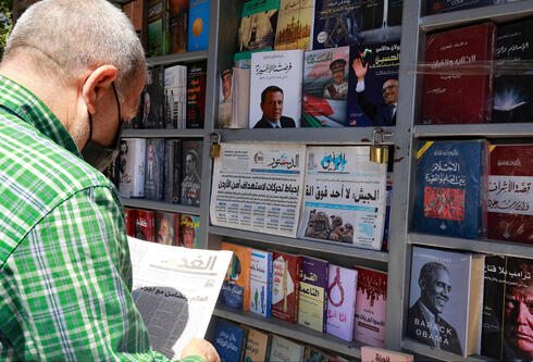 Man standing at a newspaper stand and reading about a wave of arrests following an alleged coup attempt in the Jordanian capital of Amman