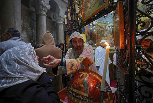 A Coptic priest gives the communion during mass on Easter Sunday at the Church of the Holy Sepulchre in Jerusalem on April 4, 2021