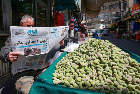 Man in Jordan's capital of Amman reads about the attempted coup