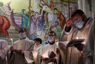 Fransiscan friars pray during mass on Easter Sunday at the Church of the Holy Sepulchre in Jerusalem, April 4, 2021