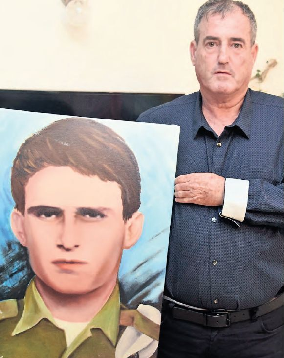 Oren Tamam holds a portrait of his late brother, Moshe