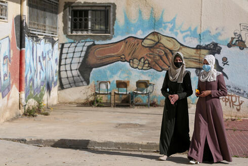 Palestinian students walk at a university in Khan Younis in the southern Gaza Strip