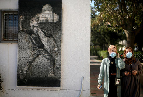 Palestinian students walk at a university in Khan Younis in the southern Gaza