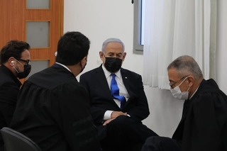 Prime Minister Benjamin speaks to his legal team as he appears in Jerusalem District Court court in on Monday
