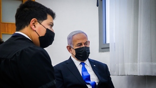 Prime Minister Benjamin Netanyahu sits with one of his attorneys at the beginning of his trial on Monday