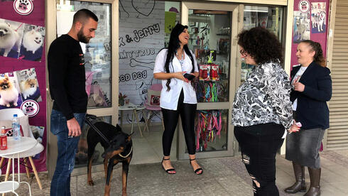 customer waits with his dog, Pablo, outside the shop of Jeje Jouly Touk,