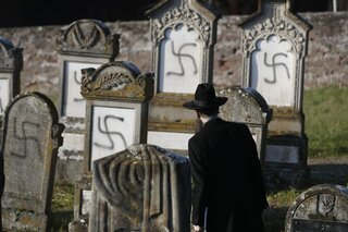 Strasbourg Chief Rabbi Harold Abraham Weill looks at vandalized tombs in the Jewish cemetery west of the French city of Strasbourg