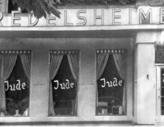 the word Jude (jew) is smeared to the windows of a shop in Berlin run by Jews. On Nov. 9, 1938