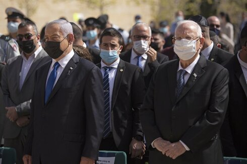 Prime Minister Benjamin Netanyahu, left, stands next to President Revin Rivlin as they attend a ceremony marking the annual Holocaust Remembrance Day, at Yad Vashem Holocaust Memorial in Jerusalem