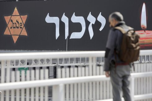 An Israeli stands as sirens mark a nationwide moment of silence in remembrance of the 6 million Jewish victims of the Holocaust, in Tel Aviv