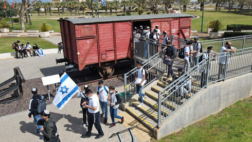 Students and teachers of Bar Ilan School visit an authentic German train, that transported Jews to extermination camps, on the Holocaust Remembrance Day in the Israeli city of Netanya