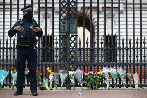 A police officer stands next to bouquets of flowers outside Buckingham Palace in London after it was announced that Prince Philip, husband of Queen Elizabeth, has died at the age of 99, April 9, 2021