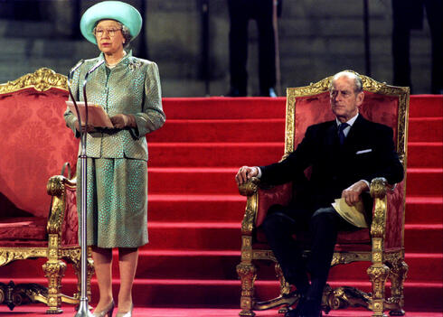 Prince Philip watches as Queen Elizabeth delivers an address to both houses of parliament at the Palace of Westminster May 5, 1995