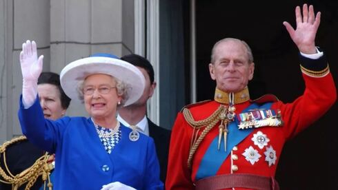 Queen Elizabeth II and Prince Philip wave from the balcony of Buckingham Palace during a flypast for the trooping of the colour, June 2003