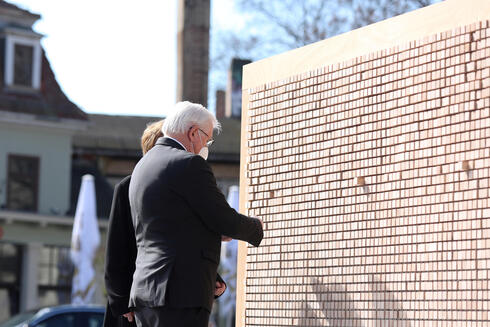 German President Steineier and wife at a commemorative wall at Buchenwald on the anniversary of its liberation