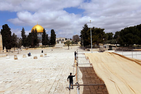 Workers put up canvases to provide shade for worshippers on Temple Mount, in preparation for the holy Muslim month of Ramadan, in Jerusalem's Old City, April 12, 2021
