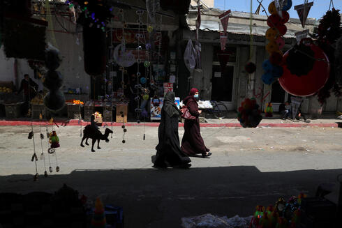 Palestinians walk as they shop at a market, ahead of the holy fasting month of Ramadan, in Gaza City April 5, 2021